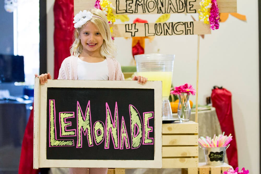 Young girl holding up a sign for her lemonade stand