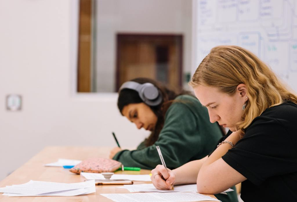 two students writing in their notebooks