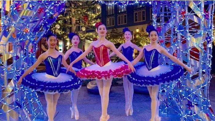 five ballerinas posing in elaborate costumes