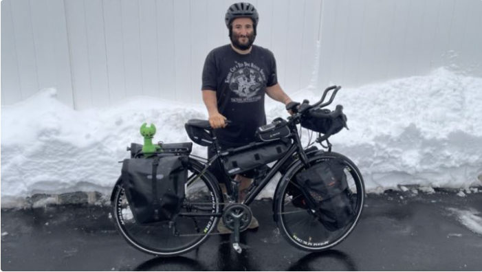 man in helmet smiling with his bicycle