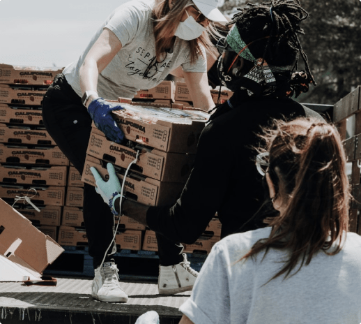 Two volunteers unloading supplies from a truck