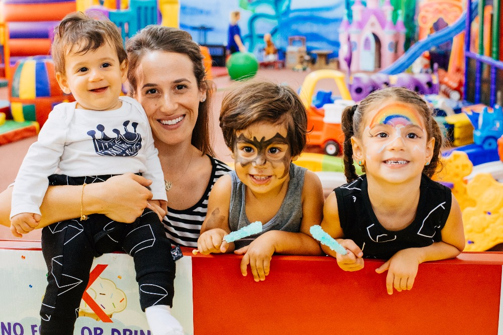 Mom and her three young kids with face painting