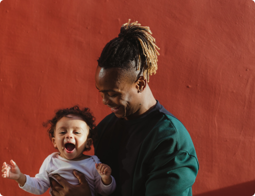Black father smiling at his child and baby smiling directly at camera