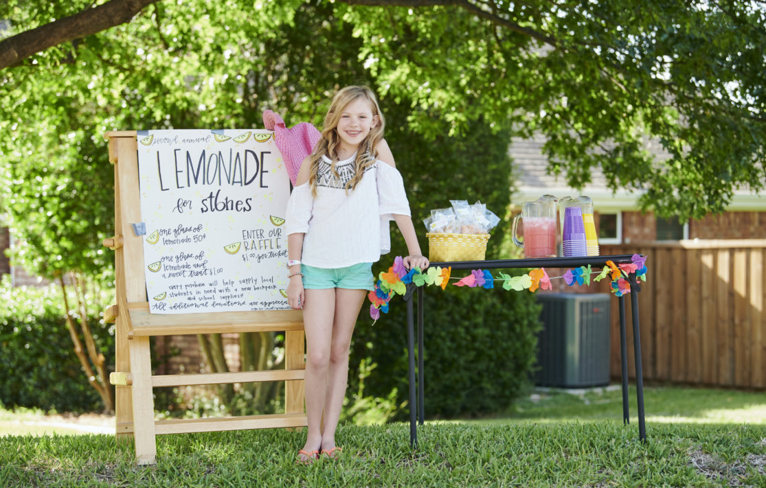 Young girl psoing in front of her lemonade stand for charity