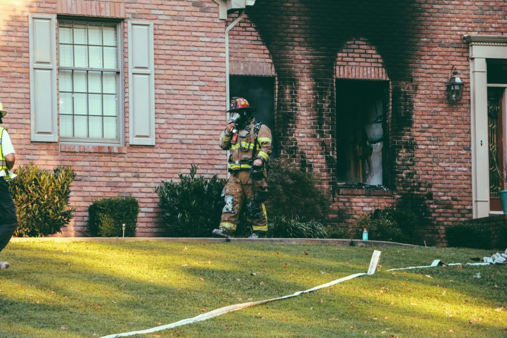 Firefighter walking out of a house
