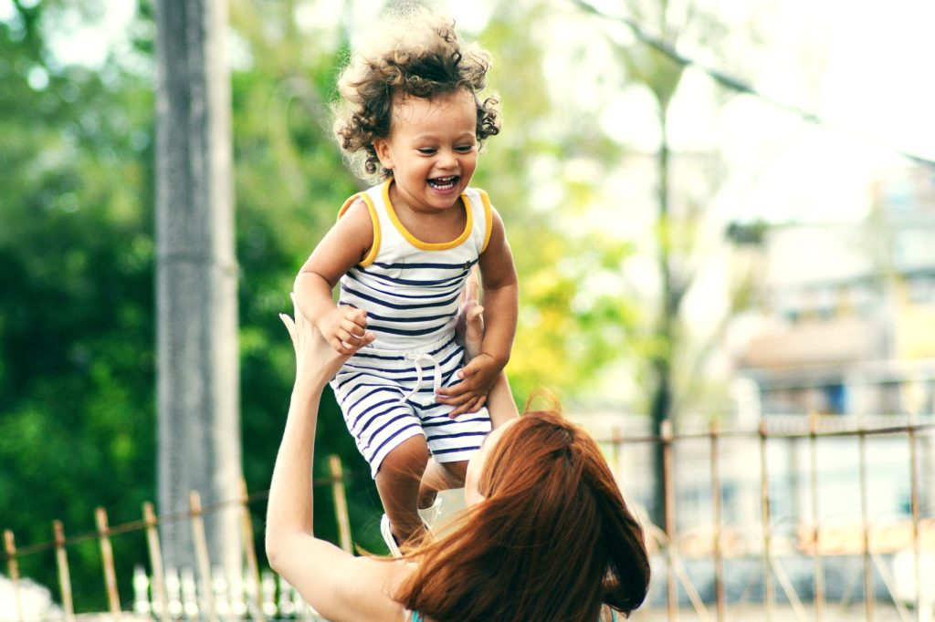 Woman holding up a small child